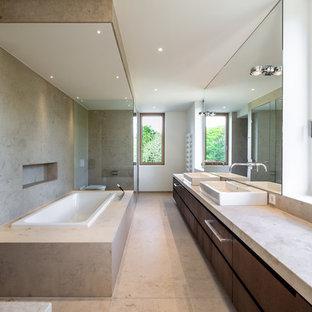 Großes Modernes Badezimmer mit flächenbündigen Schrankfronten, dunklen Holzschränken, Einbaubadewanne, Wandtoilette mit Spülkasten, beigefarbenen Fliesen, weißer Wandfarbe, Aufsatzwaschbecken, beigem Boden und beiger Waschtischplatte in München