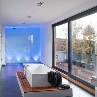 Ejemplo de cuarto de baño actual, extra grande, con bañera exenta, ducha a ras de suelo, baldosas y/o azulejos grises y paredes blancas