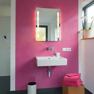 Foto di una stanza da bagno contemporanea di medie dimensioni con piastrelle grigie, pareti rosa, lavabo sospeso e piastrelle in pietra
