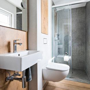 Стильный дизайн: ванная комната в современном стиле с душем в нише, инсталляцией, серой плиткой, белыми стенами, паркетным полом среднего тона, настольной раковиной, коричневым полом, душем с раздвижными дверями, тумбой под одну раковину и деревянными стенами - последний тренд
