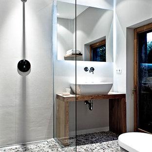 Diseño de cuarto de baño contemporáneo, pequeño, con lavabo sobreencimera, puertas de armario de madera oscura, encimera de madera, ducha abierta, paredes grises, suelo de baldosas tipo guijarro, suelo de baldosas tipo guijarro, ducha abierta y encimeras marrones