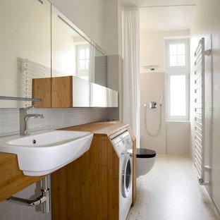 Пример оригинального дизайна: ванная комната среднего размера в современном стиле с плоскими фасадами, фасадами цвета дерева среднего тона, столешницей из дерева, белыми стенами, душем в нише, серой плиткой, удлиненной плиткой, душевой кабиной, накладной раковиной и шторкой для душа