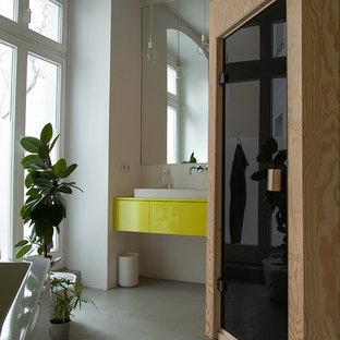 Foto di una stanza da bagno contemporanea di medie dimensioni con ante lisce, ante gialle, pareti bianche, pavimento in cemento e lavabo a bacinella