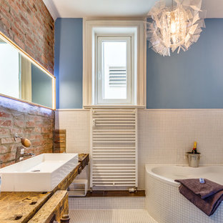 Design ideas for a large contemporary bathroom in Hamburg with a corner bath, white tiles, mosaic tiles, blue walls, mosaic tile flooring, a vessel sink and wooden worktops.