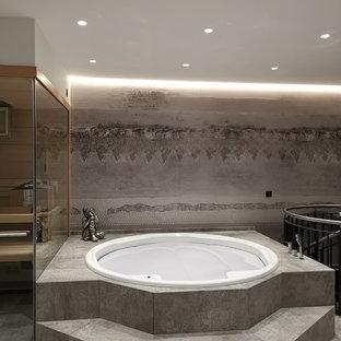 Großes Modernes Badezimmer mit Einbaubadewanne und grauem Boden in München