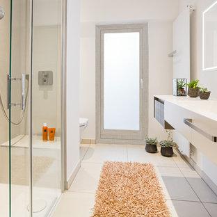 Kleines Modernes Duschbad mit flächenbündigen Schrankfronten, beigefarbenen Fliesen, weißer Wandfarbe, beigem Boden, Schiebetür-Duschabtrennung, Wandtoilette, braunen Schränken, bodengleicher Dusche, Keramikfliesen, Keramikboden, Waschtischkonsole und Mineralwerkstoff-Waschtisch in Köln