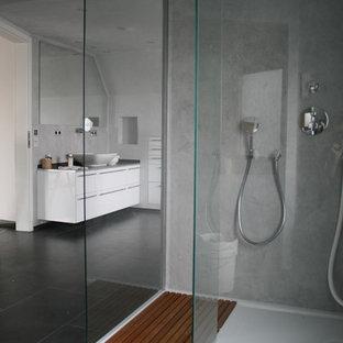 Imagen de cuarto de baño con ducha, clásico, grande, con puertas de armario blancas, ducha a ras de suelo, baldosas y/o azulejos de vidrio laminado, paredes grises, suelo vinílico, lavabo sobreencimera y encimera de madera