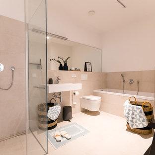 Modernes Badezimmer En Suite mit bodengleicher Dusche, Wandtoilette, beigefarbenen Fliesen, weißer Wandfarbe, Wandwaschbecken, beigem Boden, Falttür-Duschabtrennung und weißer Waschtischplatte in Köln