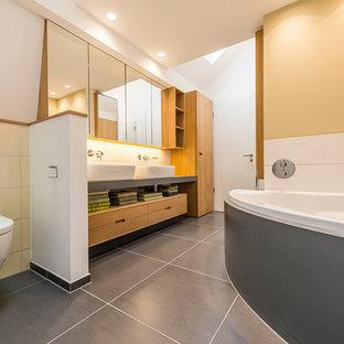 Diseño de cuarto de baño contemporáneo, de tamaño medio, con lavabo sobreencimera, puertas de armario de madera oscura, encimera de acrílico, bañera esquinera, ducha a ras de suelo, sanitario de pared, baldosas y/o azulejos grises, baldosas y/o azulejos amarillos, baldosas y/o azulejos blancos, baldosas y/o azulejos de cerámica, suelo vinílico y paredes amarillas