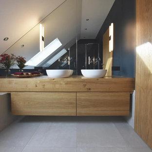 Exempel på ett mellanstort modernt brun brunt badrum med dusch, med släta luckor, skåp i mellenmörkt trä, ett platsbyggt badkar, en kantlös dusch, en vägghängd toalettstol, beige kakel, keramikplattor, blå väggar, klinkergolv i keramik, ett fristående handfat, träbänkskiva, beiget golv och dusch med gångjärnsdörr