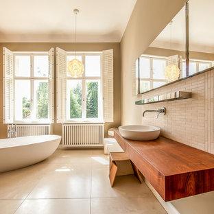 Неиссякаемый источник вдохновения для домашнего уюта: большая ванная комната в современном стиле с настольной раковиной, столешницей из дерева, отдельно стоящей ванной, бежевой плиткой, бежевыми стенами, удлиненной плиткой и коричневой столешницей