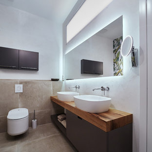 Mid-sized trendy white tile and stone tile brick floor and brown floor drop-in bathtub photo in Other with open cabinets, gray cabinets, a two-piece toilet, white walls, a vessel sink, wood countertops and brown countertops