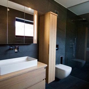 Großes Modernes Duschbad Mit Hellbraunen Holzschränken, Bodengleicher  Dusche, Wandtoilette, Schwarzen Fliesen, Schwarzer