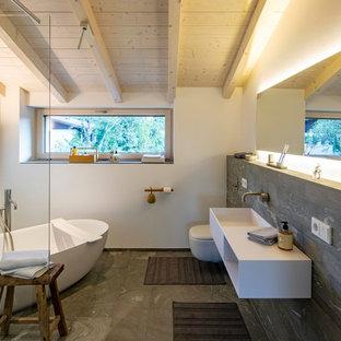 Modernes Badezimmer En Suite mit freistehender Badewanne, weißer Wandfarbe, Wandwaschbecken, grauem Boden und weißer Waschtischplatte in München