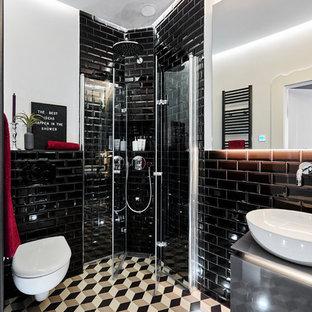 Kleines Modernes Duschbad mit grauen Schränken, Eckdusche, Wandtoilette, schwarzen Fliesen, Metrofliesen, weißer Wandfarbe, Aufsatzwaschbecken, buntem Boden, Falttür-Duschabtrennung, grauer Waschtischplatte und flächenbündigen Schrankfronten in München