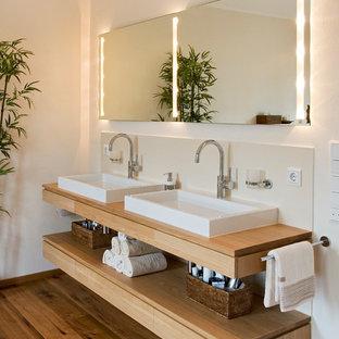 Idee per una stanza da bagno padronale design di medie dimensioni con ante lisce, vasca freestanding, piastrelle in pietra, pareti beige, pavimento in legno massello medio, lavabo a bacinella, top in legno, ante in legno chiaro, piastrelle beige e top marrone