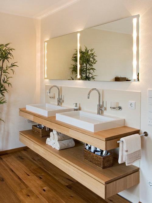 Badezimmer mit holz waschtisch und braunem holzboden ideen ...