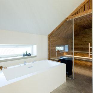 Mittelgroßes Modernes Badezimmer mit freistehender Badewanne, weißer Wandfarbe, Betonboden, Sauna und grauem Boden in München