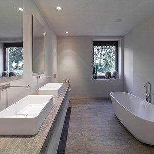 Modelo de cuarto de baño minimalista, grande, con lavabo sobreencimera, bañera exenta, paredes grises, losas de piedra, encimera de piedra caliza y suelo de piedra caliza