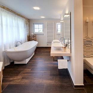 Großes Mediterranes Badezimmer En Suite mit offenen Schränken, braunen Schränken, freistehender Badewanne, offener Dusche, Toilette mit Aufsatzspülkasten, braunen Fliesen, Porzellanfliesen, brauner Wandfarbe, Porzellan-Bodenfliesen, Aufsatzwaschbecken, Waschtisch aus Holz, braunem Boden, offener Dusche und beiger Waschtischplatte in München