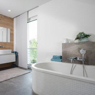 Mittelgroßes Modernes Duschbad mit flächenbündigen Schrankfronten, weißen Schränken, freistehender Badewanne, weißer Wandfarbe, Zementfliesen, Aufsatzwaschbecken und grauem Boden in Frankfurt am Main