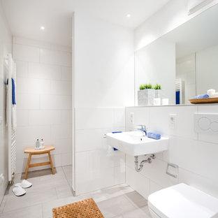 Kleines Modernes Duschbad mit bodengleicher Dusche, Wandtoilette, weißen Fliesen, weißer Wandfarbe, Wandwaschbecken, grauem Boden, offener Dusche und Porzellanfliesen in Berlin
