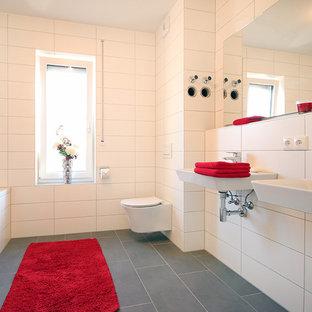 Immagine di una stanza da bagno con doccia minimal di medie dimensioni con piastrelle bianche, pavimento grigio, vasca da incasso, WC sospeso, pareti bianche, lavabo sospeso, vasca/doccia, piastrelle in ceramica e pavimento con cementine