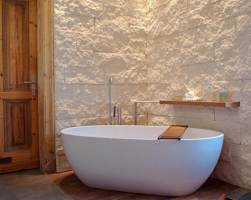 Modernes Badezimmer Mit Freistehender Badewanne, Steinfliesen, Beiger  Wandfarbe Und Dunklem Holzboden In Düsseldorf