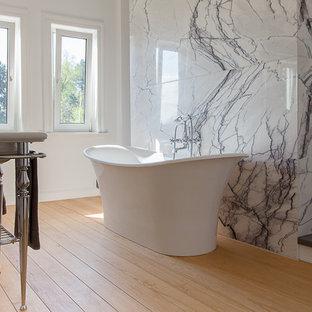 Foto på ett stort funkis badrum, med ett avlångt handfat, ett fristående badkar, stenkakel, vita väggar, mellanmörkt trägolv, svart kakel och vit kakel