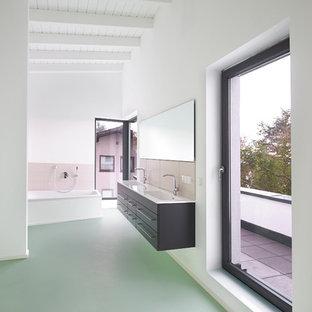 Immagine di una grande stanza da bagno con doccia minimal con ante lisce, ante grigie, vasca ad angolo, piastrelle rosa, piastrelle in ceramica, pareti bianche, top in legno, pavimento verde e top bianco