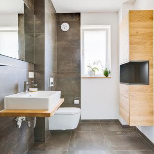 Modernes Badezimmer mit grauen Fliesen, weißer Wandfarbe, Aufsatzwaschbecken, Waschtisch aus Holz, grauem Boden, brauner Waschtischplatte und Einzelwaschbecken in Nürnberg