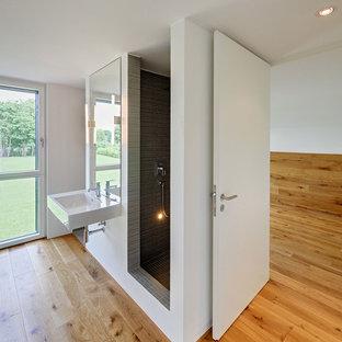 Immagine di una grande stanza da bagno design con doccia alcova, piastrelle grigie, piastrelle a listelli, pareti bianche, pavimento in legno massello medio e lavabo sospeso