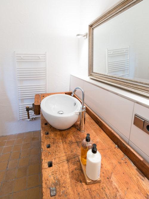 Salle de bain avec un plan de toilette en bois et un sol en carreau de terre - Taille moyenne salle de bain ...