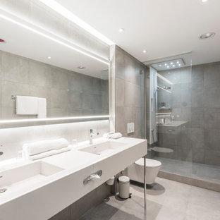 Großes Modernes Duschbad mit offenen Schränken, Duschnische, Wandtoilette, grauen Fliesen, Porzellanfliesen, Porzellan-Bodenfliesen, integriertem Waschbecken, grauem Boden und weißer Waschtischplatte in Frankfurt am Main