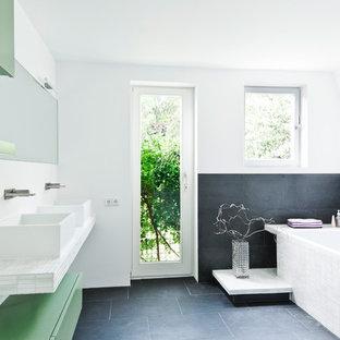 Foto di una stanza da bagno nordica di medie dimensioni con lavabo a bacinella, ante lisce, ante verdi, top piastrellato, piastrelle nere, pareti bianche, vasca da incasso, lastra di pietra e pavimento in ardesia