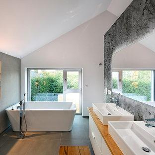 Mittelgroßes Modernes Duschbad mit flächenbündigen Schrankfronten, weißen Schränken, freistehender Badewanne, Wandtoilette, Aufsatzwaschbecken, Waschtisch aus Holz, grauem Boden, grauer Wandfarbe, Duschbadewanne, Zementfliesen und offener Dusche in Nürnberg
