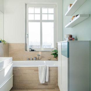 Imagen de cuarto de baño actual, de tamaño medio, con puertas de armario turquesas, bañera encastrada, sanitario de pared, baldosas y/o azulejos beige y lavabo integrado