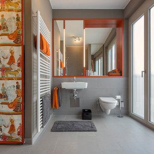 На фото: ванная комната среднего размера в современном стиле с инсталляцией, серой плиткой, подвесной раковиной, серыми стенами, открытыми фасадами и оранжевыми фасадами с