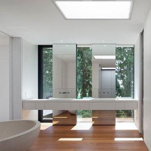 Imagen de cuarto de baño contemporáneo, de tamaño medio, con bañera exenta, baldosas y/o azulejos con efecto espejo, armarios con paneles lisos, puertas de armario blancas, paredes blancas y suelo de madera en tonos medios