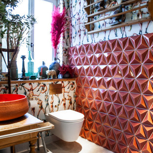 Small eclectic 3/4 bathroom in Hamburg with distressed cabinets, a curbless shower, a wall-mount toilet, pink tile, ceramic tile, multi-coloured walls, terrazzo floors, a vessel sink, tile benchtops, grey floor, a sliding shower screen, pink benchtops, a single vanity, a freestanding vanity, wallpaper and wallpaper.