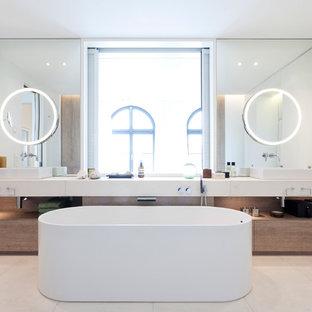 Inredning av ett modernt mycket stort en-suite badrum, med släta luckor, vita skåp, ett fristående badkar, en kantlös dusch, en vägghängd toalettstol, beige kakel, stenhäll, vita väggar, kalkstensgolv, ett fristående handfat och bänkskiva i kalksten
