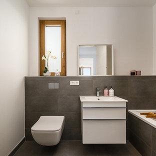Kleines Modernes Duschbad mit flächenbündigen Schrankfronten, weißen Schränken, Einbaubadewanne, Wandtoilette, grauen Fliesen, Zementfliesen, weißer Wandfarbe, Waschtischkonsole und grauem Boden in München
