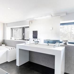Großes Modernes Badezimmer mit offenen Schränken, weißen Schränken, Badewanne in Nische, grauen Fliesen, weißer Wandfarbe, Trogwaschbecken, schwarzem Boden und weißer Waschtischplatte in Düsseldorf