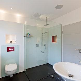Imagen de cuarto de baño con ducha, minimalista, de tamaño medio, con ducha a ras de suelo, sanitario de dos piezas, baldosas y/o azulejos azules, baldosas y/o azulejos de vidrio laminado, paredes blancas, lavabo sobreencimera, encimera de granito, suelo negro, ducha abierta y encimeras negras