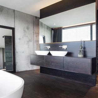 Diseño de cuarto de baño con ducha, actual, grande, con armarios con paneles lisos, puertas de armario de madera en tonos medios, bañera exenta, baldosas y/o azulejos marrones, baldosas y/o azulejos de cemento, paredes grises, suelo de bambú, lavabo sobreencimera, encimera de acrílico y suelo marrón