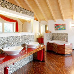 Example of a huge eclectic multicolored tile and ceramic tile dark wood floor corner bathtub design in Stuttgart with white walls, a vessel sink and wood countertops