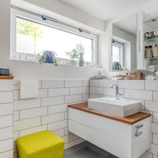 Kleines Modernes Badezimmer mit flächenbündigen Schrankfronten, weißen Schränken, weißen Fliesen, weißer Wandfarbe, Aufsatzwaschbecken, Waschtisch aus Holz, grauem Boden, brauner Waschtischplatte, Einzelwaschbecken und schwebendem Waschtisch in München