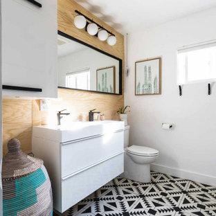 Diseño de cuarto de baño con ducha y madera, actual, de tamaño medio, madera, con armarios con paneles lisos, puertas de armario blancas, sanitario de una pieza, paredes blancas, lavabo sobreencimera, encimera de madera, encimeras blancas, suelo multicolor y madera