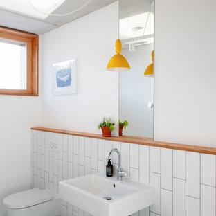 Esempio di una piccola stanza da bagno per bambini scandinava con WC sospeso, piastrelle bianche, pareti bianche, lavabo sospeso, doccia a filo pavimento, piastrelle in ceramica, pavimento con piastrelle in ceramica, top in superficie solida, pavimento verde, doccia aperta, nicchia, un lavabo, mobile bagno sospeso e soffitto ribassato