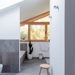 Photo of a scandinavian 3/4 bathroom in Munich with a drop-in tub, an open shower, a bidet, gray tile, white walls, grey floor and an open shower.